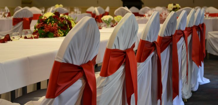White tieback chaircovers with red satin sash. Styled by Greenstone Events.