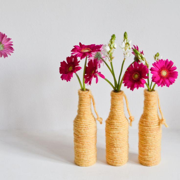 Een leeg flesje is bekleed met wol en is hiermee omgetoverd tot een sfeervol vaasje wat er weer helemaal bijhoort. Erg mooi met een paar bloemen erin.