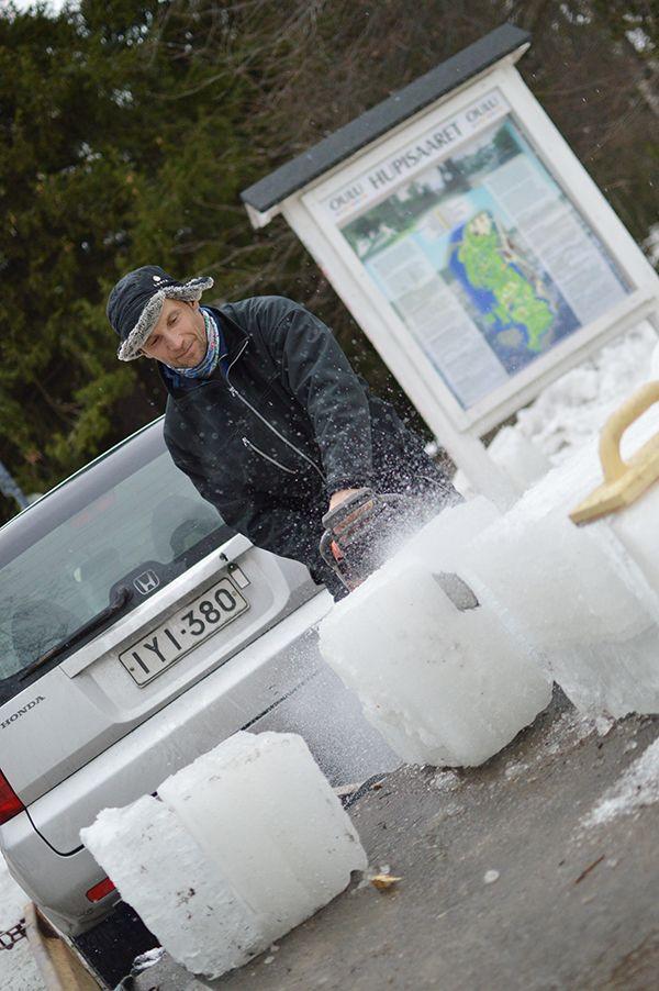 Lumirakentamisen asiantuntija Seppo Mäkinen lohkoo moottorisahalla jääkuutioita pienemmiksi. Lumenveistopajassa käytetään rakennusmateriaaleina vain lunta ja jäätä. Oulu (Finland)