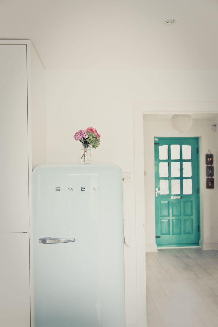 Fresh flowers smeg fridge and a white kitchen