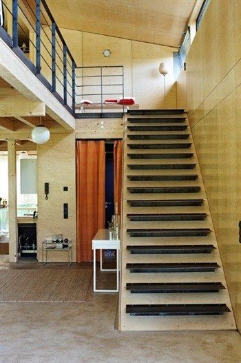Light wood staircase with black steps leading to open airy plan hall and polished concrete flooring