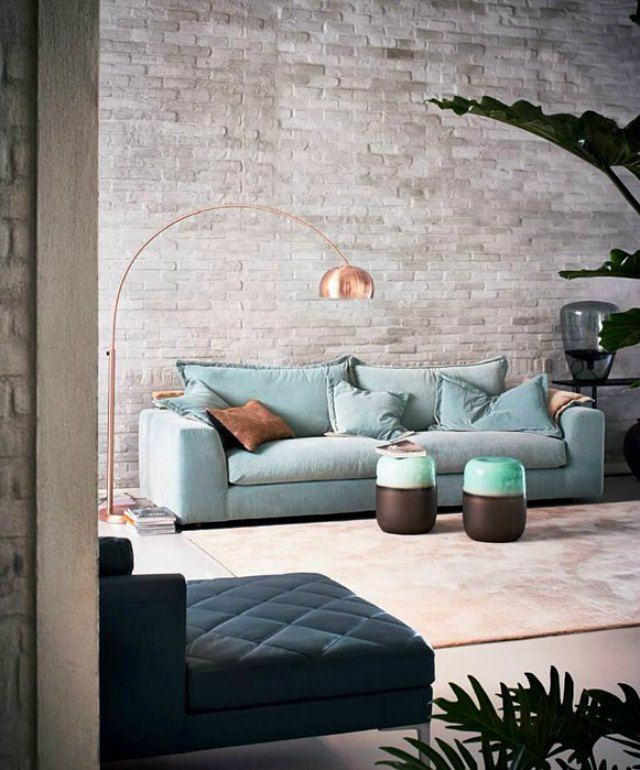 A contemporary setup with a light blue sofa and a copper floor lamp hanging over it and a grey brick accent wall on the background.