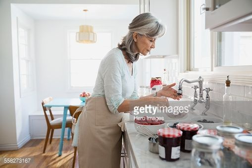 Stock Photo : Woman making jam with fresh berries in kitchen