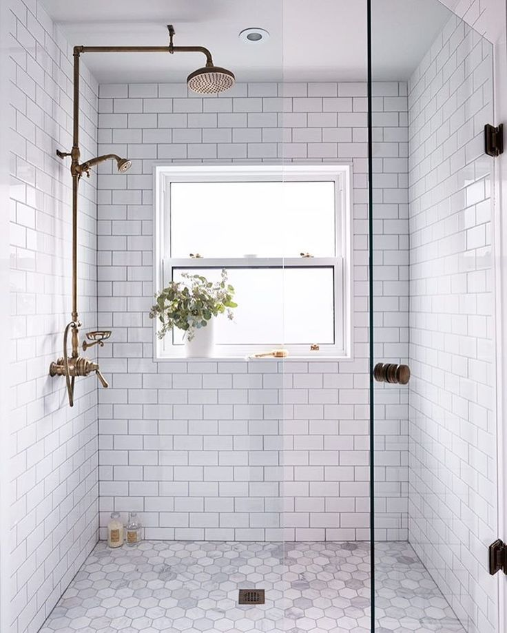 This subway tile shower with a window and gold acc…