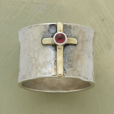 """A visit to a European cathedral prompted the design of this hand-hammered sterling silver band. The 14kt gold cross bears a garnet cabochon. Whole and half sizes 5 to 9 1/2. 5/8""""W."""