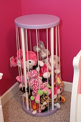 """The toy """"cage"""" Brad created from scratch to put all our our daughter's babies, stuffed animals, etc.  He used 4 dowel rods and a bunch of bungee cords so that he could get his toys in and out with ease.  Here it is with a bunch of her stuff in it."""