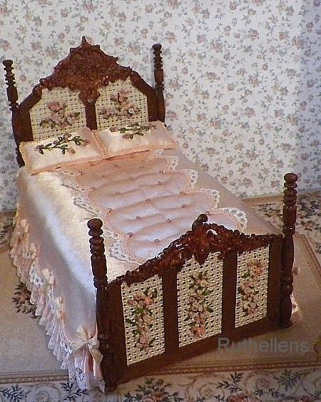 Rich maple stained wood and fancy appliques show off the embroidered cane foot and head inserts. Silk satin peach dust ruffle with peach lace. Same silk for the bedspread with a fancy padded panel on the top Two embroidered pillows. Edges trimmed in satin with silk bows. Gorgeous bed.....