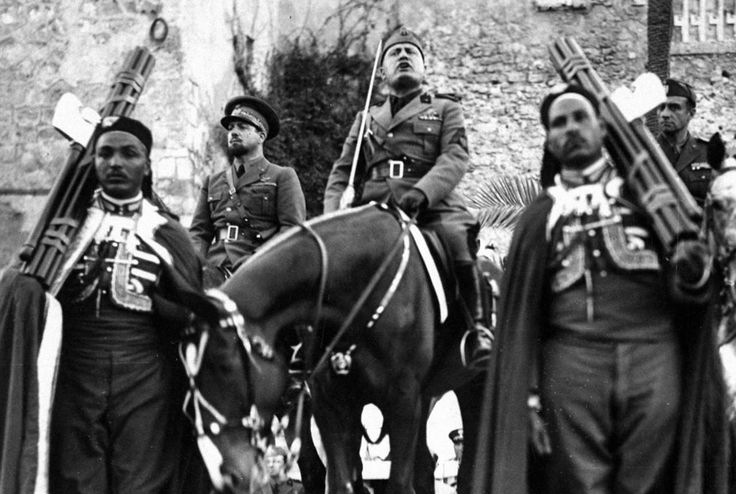 Benito Mussolini (on the horse) in Tripoli, Libya, probably c. 1939. The honor guard of two Libyan soldiers hold fasciae, symbols of authority and the right to impose the death penalty in ancient Rome, which Mussolini had adopted as the symbol of his Fascist Party (deriving its name from fasciae). In the background of the left is Italo Balbo, the only Air Masrhal of Italy at the time and Governor of Libya. Balbo was killed by friendly fire on June 28, 1940.