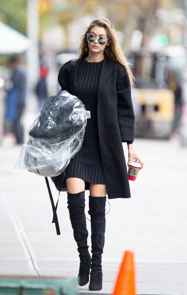 Gigi Hadid wears a black coat, ribbed dress, and thigh-high boots