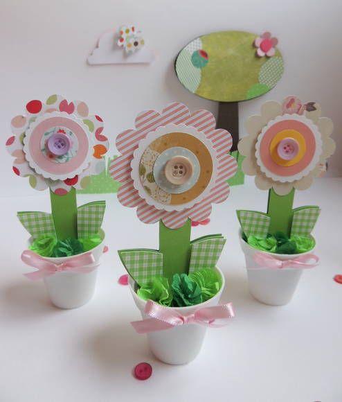 Enfeite para ser colocado na mesa do bolo ou outro lugar que preferir.  O vaso é de plástico na cor branca, a flor é feita de papel scrapbook, a grama é papel de seda rococó.  Quantidade mínima para a compra é de 10 unidades. R$ 3,50