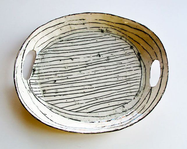 Hand build tray; dark glaze in design then sponge off and dip in translucent white-ish glaze.