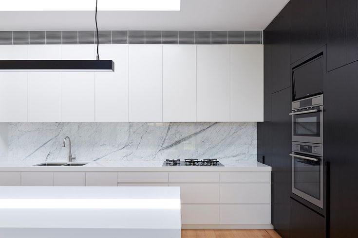 Kitchen: white handleless cabinets, black wooden feature cabinets, white marble splashback, white stone benchtops, minimalist gas cooktop, black linear pendant light, skylight above island