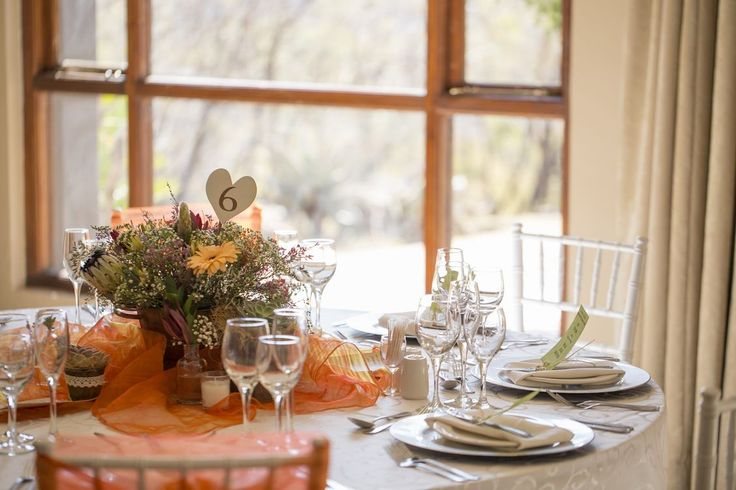 Orange hues accompanied by shades of greens, harnessing autumn colours tying in with the local stand stone feature walls of our Tswana Kraal venue.
