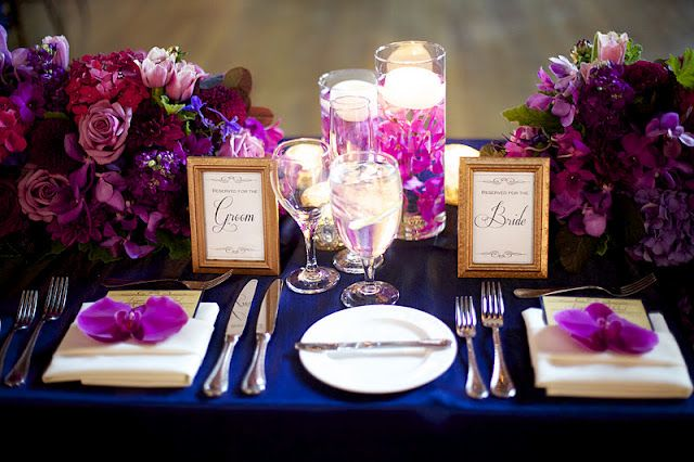 navy blue table cloth, candle centerpieces, shades of purple and blue flowers, with gold or silver accents