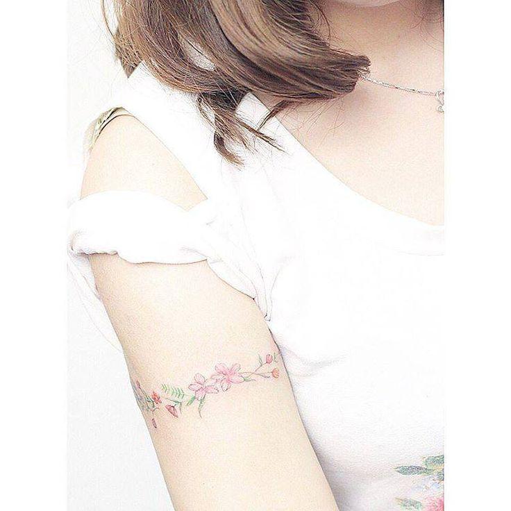 Flower bracelet tattoo on the right upper arm.