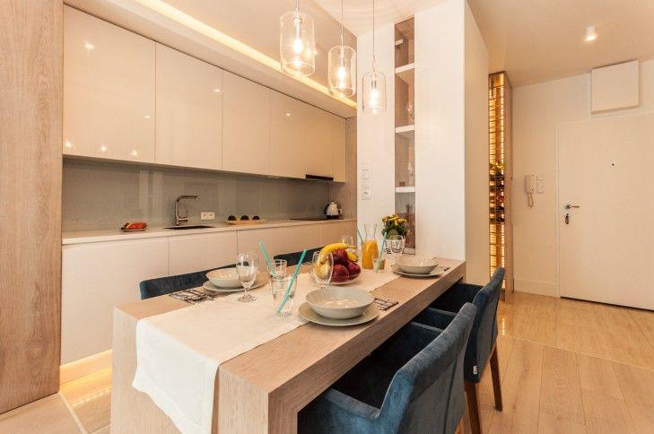 Aranżacja jadalni w niewielkim mieszkaniu w Warszawie. Pastelowe kolory i połyskujące faktury sprawiają, że wnętrze wydaje się większe niż w rzeczywistości.