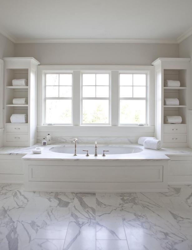 bathroom with white wood paneled droptub flanked by white vertical bathroom cabinets gray bathroom walls paint color and marble tiles bathroom floor