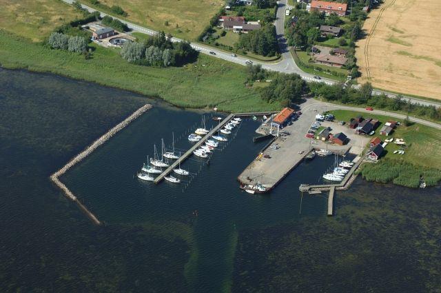 Udvidelsen i 2012 af det vestlige lystbådebassin i Bogø Havn, fotograferet i juli 2012. Den gamle bølgebryder fra 1943 er fjernet og erstattet af en ny med knæk ca. 50 m længere mod vest. Dermed blev der plads til både også på vestsiden af den i 1998 anlagte bro. Foto: Kort & Matrikelstyrelsen