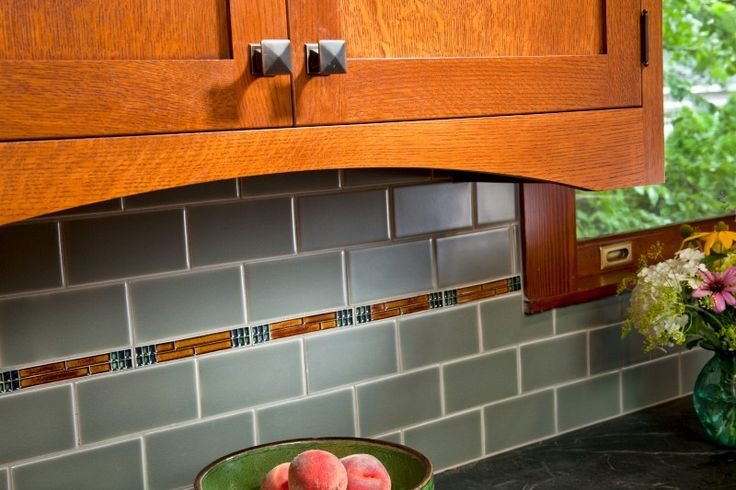 Handcrafted satin-stained crackle subway tile and decorative glass tile in the Arts & Crafts style were carefully laid out and installed. The gently curved arch of the undercabinet valance conceals task lighting, softening the kitchen's angles and mimicking the arch of the range hood. Burnished antique knobs and pulls used throughout are new, but have vintage styling.