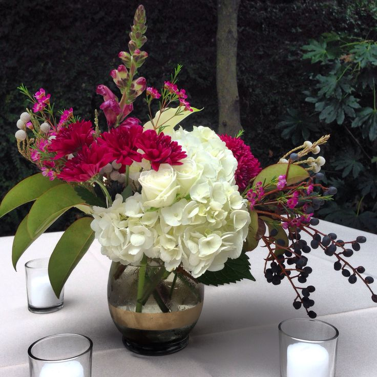 Centerpiece of white hydrangeas plum cushions silver