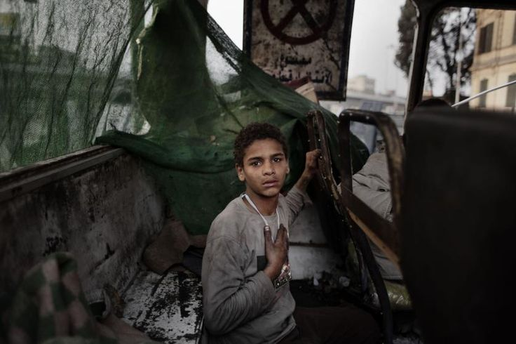 A young Egyptian protestor inside the shell of a burned out bus used as a barricade at the entrance to Tahrir Square, Cairo, Feb. 7, 2011.