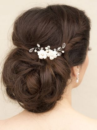 Hand beaded ceramic flower bridal hair vine comb in a low chignon bridal hairstyle by Hair Comes the Bride.