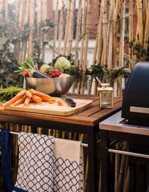 Zona cucina all'aperto con tagliere e tante verdure accanto a una griglia - IKEA