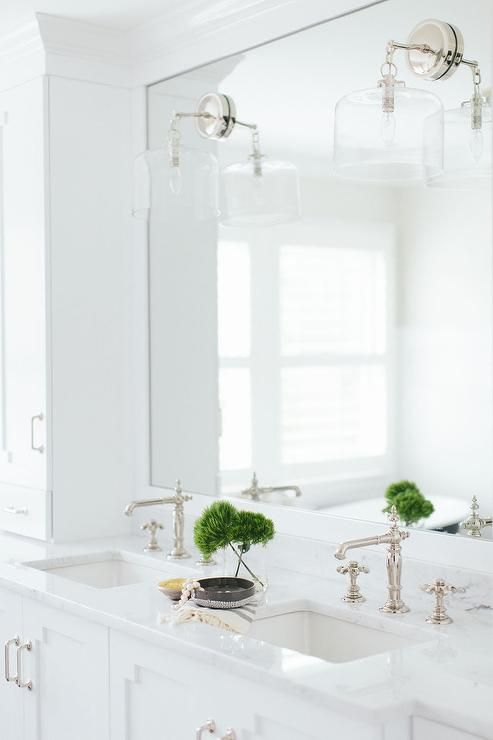 White bathroom features a long single washstand divided into his and hers sections topped with white marble fitted with his and hers sinks and vintage style faucets under a framed mirror illuminated by glass wall sconces.