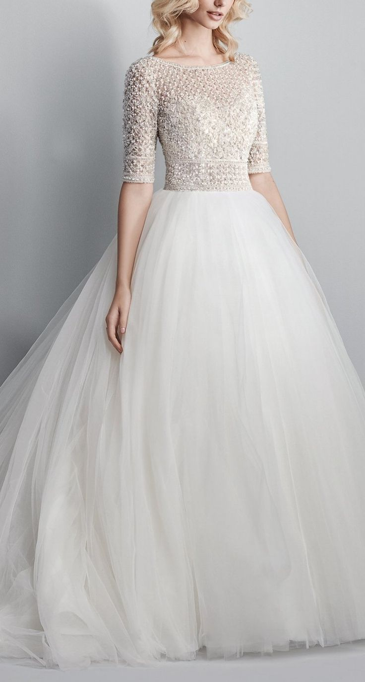Sparkle into the night with this glittering rockstar wedding dress.  Sottero and Midgley's Allen is a show-stopping ballgown featuring a sheer bodice of Swarovski crystals and beading atop a voluminous tulle skirt. Complete with half-sleeves, an elegant illusion bateau over sweetheart neckline, and sexy open back. Finished with crystal buttons over zipper closure.