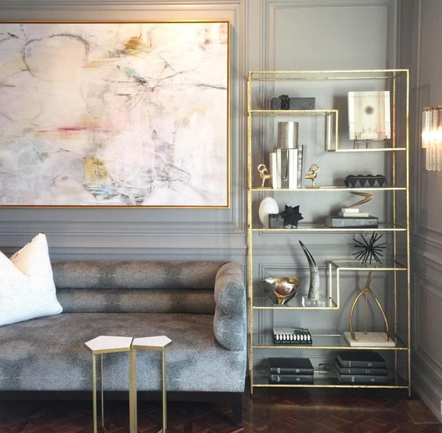 Soft abstract painting in neutral room with lots of grey and gold
