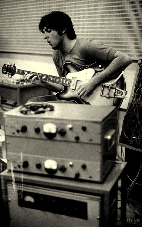 Paul McCartney in the recording studio, playing a right-handed Gibson ES-335 with Bigsby, upside down.