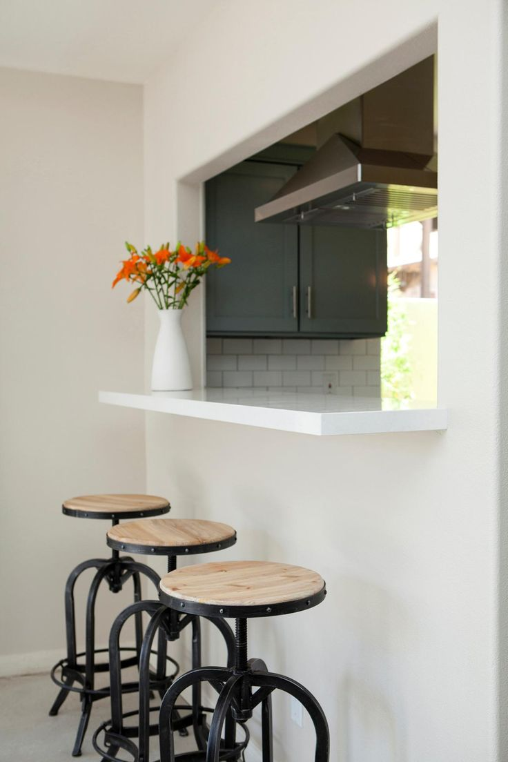 this white kitchen was updated with a large cut out into the dining room breakfast bar