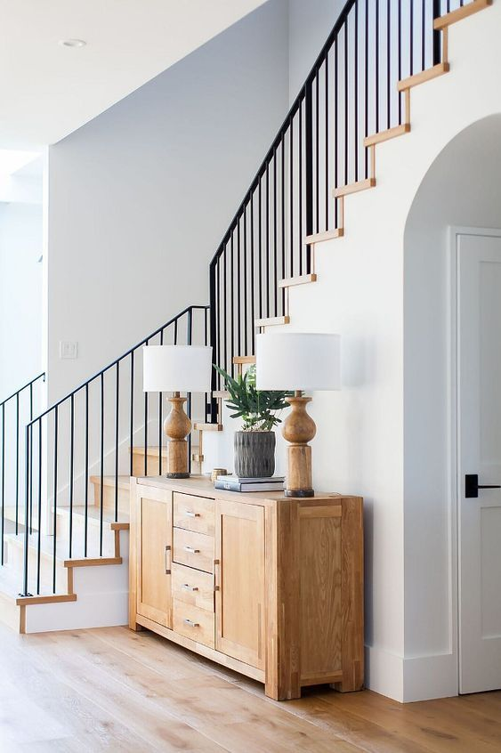 Modern farmhouse foyer features a custom staircase with wrought iron stair railing - Home Bunch