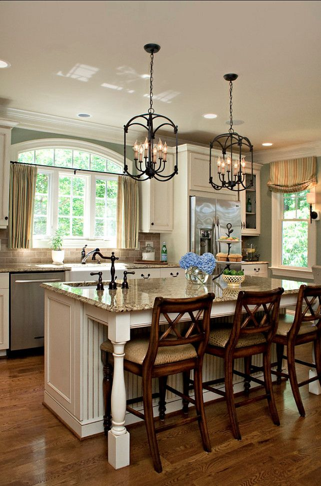 I like the two windows and the window treatments in this kitchen. I alos love the pendant lights and the the two sinks.