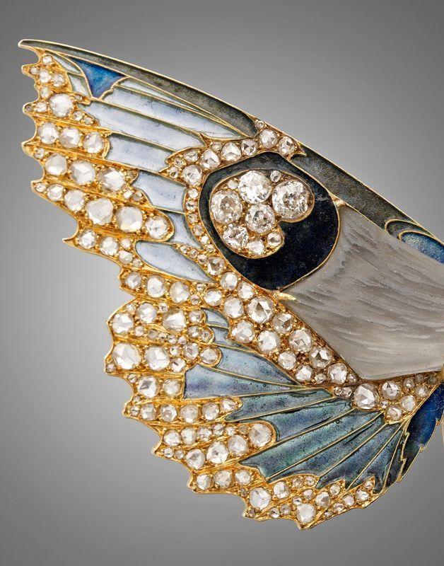 René Lalique, Rare et importante broche-pendentif devant de corsageen or jaune stylisée de deux papillons de nuit en vol, les corps en pâte de verre grise moulée au naturel, les ailes émaillées polychromes en pique-à-jour et serties de diamants taillées en rose et à l'ancienne.
