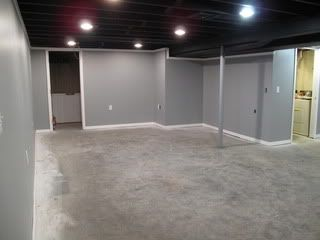 Grey basement with black, painted ceiling and grey concrete floors.