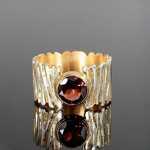 Pierścionek zrobiony w całości ręcznie ze srebra złoconego w którym został oprawiony piękny krwisto czerwony granat rodolit ( średnica 7mm). Na szerokiej obrączce (10mm) został wyrzeźbiony wzór przypominający zebrę. Wżłobienia wzoru na obrączce zostały podkreślone złotem, pozostałe powierzchnie srebra przetarte i wykończone na wysoki połysk. Efektowna ponadczasowa ozdoba, w której żadna kobieta nie pozostanie niezauważona. Rozmiar jubilerski 14, ze względu na szeroką obrączkę polecam dla ...