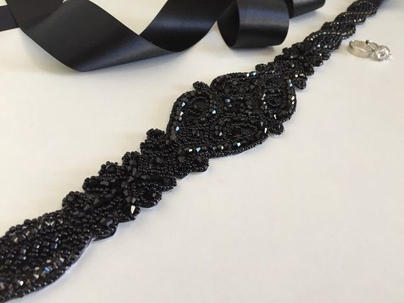 This beautiful Black encrusted sash is a petite glam statement for the bride who wants a bit of romance on her big day or for a bit of bling for your Bridal Party . Extra sparkle is illuminated by the Black and midnight black silver glass beads.  **This piece is handmade and ships within 4 WEEKS from purchase date** RUSH ORDERS available for an additional $30.00 (5 DAY PRODUCTION time plus 2-3 business days shipping)…