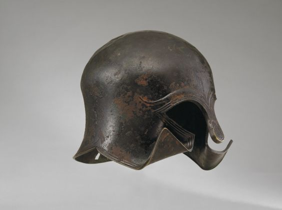 Corinthian helmet, 6th century B.C. The eyebrows look like a stylization of bulls' horns, a symbol of both courage and strength. This helmet was once dedicated as a votive offering in a sanctuary and affixed by a squarish hole in the middle of the nape. The cheekflaps were turned up at the lower corners to prevent reuse, 22 cm high. Private collection George Ortiz