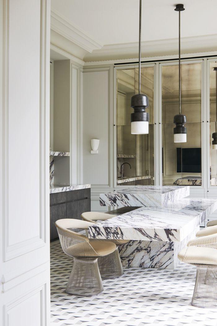 Dans la cuisine, les effets de matières se mélangent entre la pierre du sol et l'îlot en marbre Breccia Vagli Viola signé Obumex. Tout autour, les fauteuils de Warren Platner (Knoll). Suspension Fingi d'Éric Schmitt.