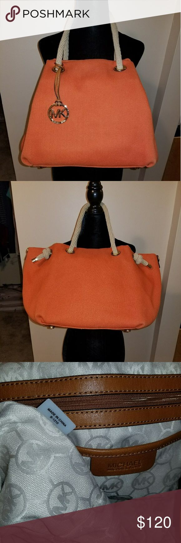 EUC Michael Kors large Fulton canvas tote This is a gorgeous nautical purse in a bright orange canvas with tan rope details and gold accents. It has 4 inside slip pockets and 1 zipper pocket, plus there is a key keeper. Very roomy, and can be used with the sides folded in or left out. Michael Kors Bags Totes