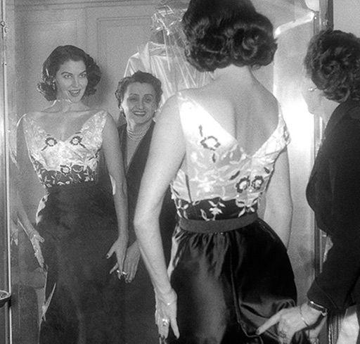"""Ava Garner mentre, aiutata da una costumista, si sistema l'abito di scena per le riprese de La Contessa scalza (1954) MOSTRA FOTOGRAFICA """"BACKSTAGE A CINECITTA'"""" alla 67ESIMA EDIZIONE DEL FESTIVAL DI CANNES"""