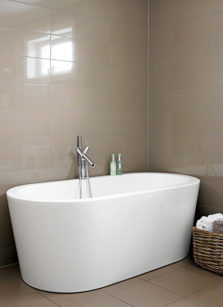 Med et enkelt lerret, i form av grå fliser, og få detaljer, kommer det stilige badekaret til sin rett. Plassert rett på gulvet med sine runde kanter ser det nesten ut som en gammeldags badebalje.