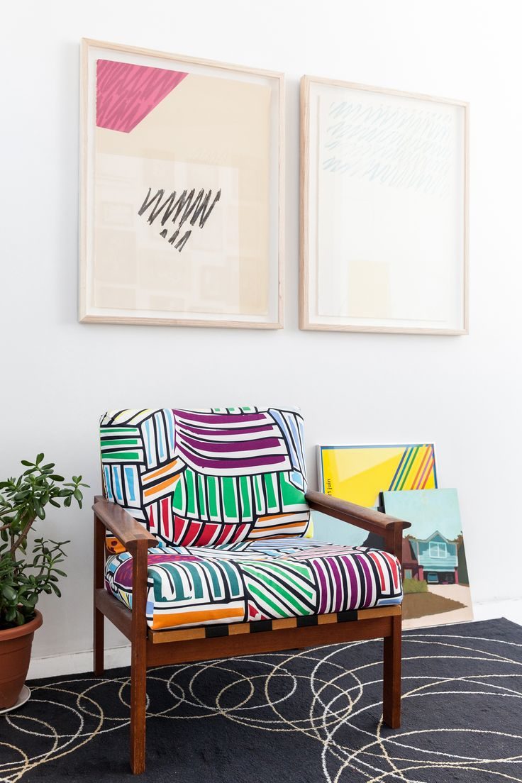 Abstract art pieces hung above bright, patterned armchair