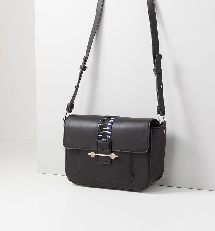 Diese kleine Handtasche hebt sich mit ihrem glänzenden Schmuckband und dem goldenen Metallstäbchen von anderen ab. Sie hat einen verstellbaren Schulterriemen, ein kleines Fach unterhalb des Verschlussriegels, 2 Innenfächer und Ton in Ton gehaltene Nähte.