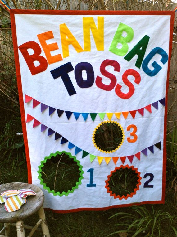 Bean Bag Toss, Rainbow Theme, bright and colorful made of heavy weight duck canvas, eco-felted lettering each stitched around the outside with white thread and mini rainbow flow bunting flags sewn on. 3 Colors of rick-rac around each hole.  There is a ribbon loop on each of the top corners to hang it by. Canvas size is 36 wide by 48 tall. Comes with 6 durable bean bags filled with real dried beans. Bean Bags are about 4 in diameter and double stiched. This is a tough and durable game for…