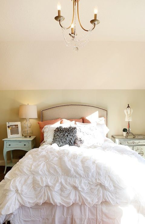 source: Utah Valley Parade of Homes website Sweet girl's room with beige headboard with nailhead trim accented with white ruffled bedding and gray ruffled pillow flanked by mismatched nightstands: Distressed turquoise nightstand with glass double gourd lamp on side of bed as well as etched mirrored nightstand on the other side.