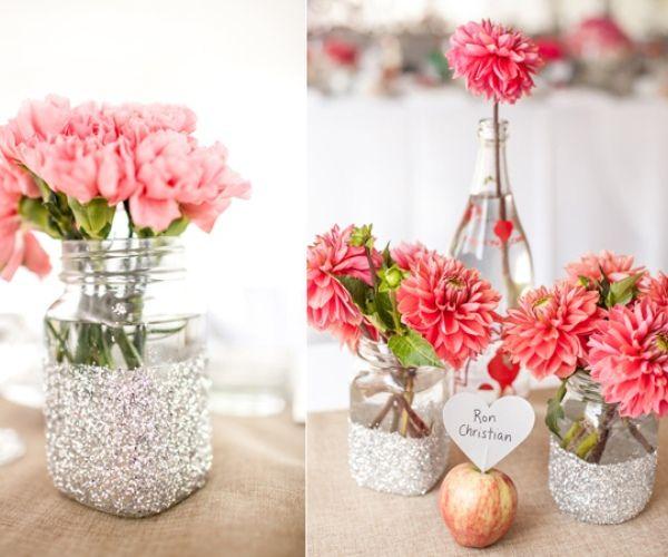 Os potes e garrafinhas são decorados com glitter e o centro é arrematado com uma maçã com uma plaquinha fixada por palito, que serve pra indicar o lugar do convidado.