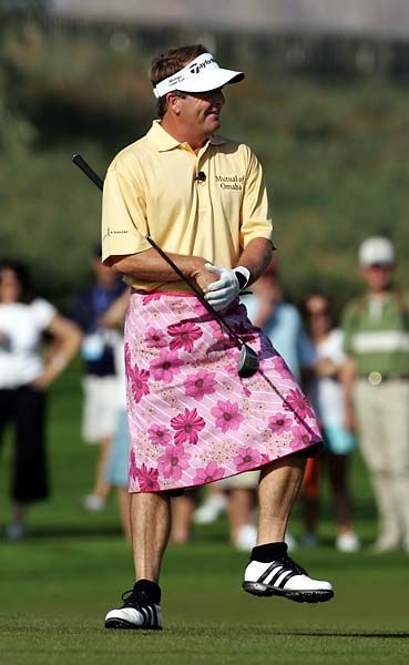 Fred Funk prepares to hit his approach shot wearing a floral pink skirt, given to him by Annika Sorenstam after she outdrove him on the third hole on the first day of the Skins Game at Trilogy Golf Club in La Quinta, Calif., Saturday, Nov. 26, 2005.