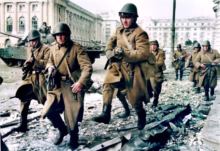 Soldiers run for cover during crossfire between pro-Ceaucescu troops and anti-regime supporters near the Republican square in Bucharest.
